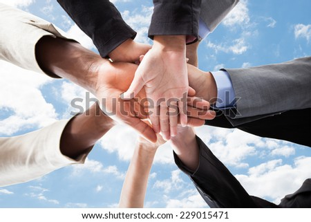 Closeup of multiethnic business people\'s hands on top of each other symbolizing unity against sky