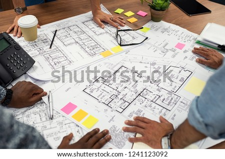 Closeup of multiethnic hands on blueprints at architects office. Team of designer and engineers working together on new residence complex. Top view of blue prints layout of house on wooden table.