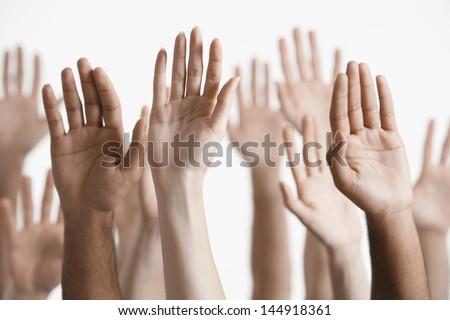 Closeup of multiethnic men and women raising hands against white background Stock photo ©