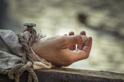 Closeup of nailed hand on wooden cross as a reenactment of the crucifixion of Jesus Christ.