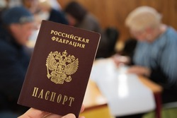 Closeup of national passport of the Russian Federation in the hand on the background of blurry people at the elections