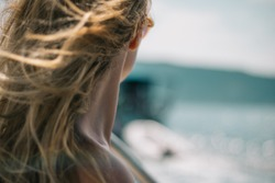 Closeup of neck of a girl looking something in the distance with wind in her hair. Woman body part on the beach - focus on the neck. Anonymous, no visible face.