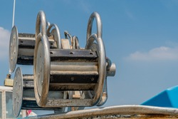 Closeup of netting spool mechanism on small fishing trawler with blue sky in background.
