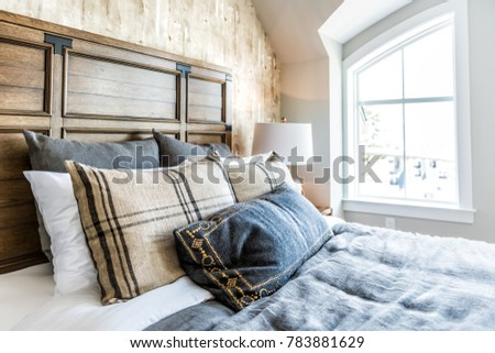 Closeup of new bed comforter with headboard, side table, lamp, decorative pillows in bedroom in staging model home, house or apartment by window with sunlight #783881629