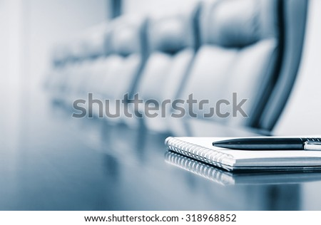 Closeup of notepad for agenda kept on table in empty corporate conference room before business meeting in blue tone