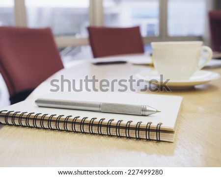 Closeup of notepad in conference modern style room interior. Agenda on table with coffee in empty corporate conference room.