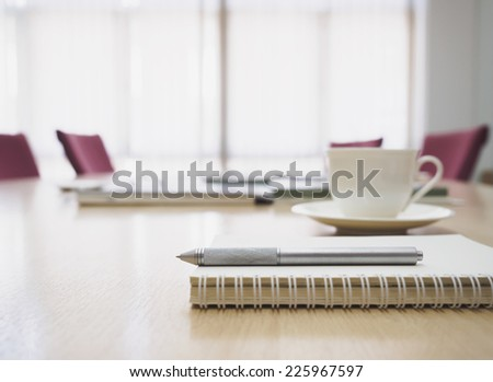 Closeup of notepad in Meeting room interior with coffee and book
