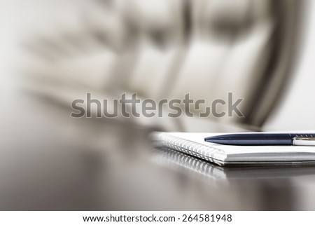 Closeup of notepad kept on table in empty conference room, motion blur