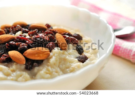 Closeup of nutritious oatmeal topped with raisins and nuts for a healthy breakfast. Also for healthy lifestyle, diet and nutrition, and food and beverage concepts.