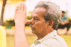 Closeup of of senior man doing alternate Nostril Breathing exercise or nadi shodhana pranayama at park - Concept of healthy active old people lifestyle.