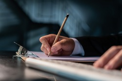 Closeup of office manager in suit holding a pencil with right hand, writing on a blank paper in the clipboard. Planning, office work, no face. Concept of contract