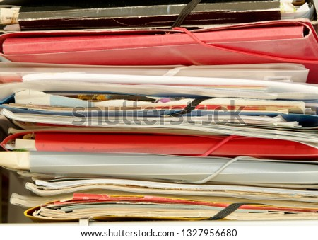 closeup of office shelf with lying folders filled with collected papers and stored publications, leaflets, and instructions