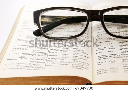 closeup of old dictionary and black glasses