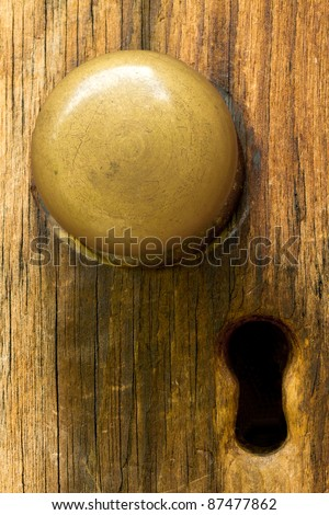Closeup of old fashioned door knob on wooden door and keyhole.