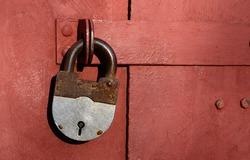 Closeup of old lock on red metal garage door