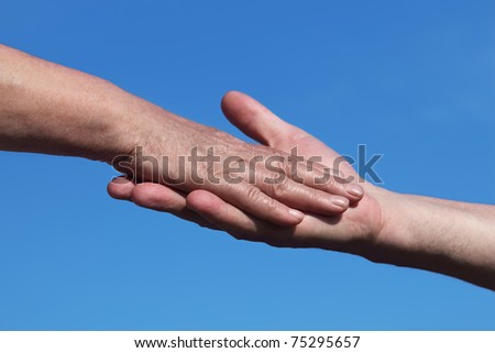 closeup of old man holding hand of old woman, blue sky