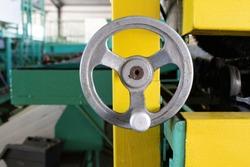 Closeup of old, metal, mechanical crank inside factory building