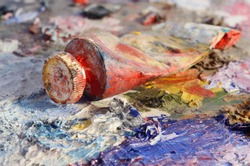 Closeup of old oil paint tube with red colour lying on dirty artistic palette ,background for creative art design