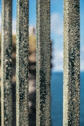 Closeup of old rusty metal fence on rocky cliff over endless blue sea on sunny day