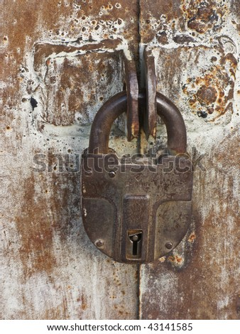 Closeup of old rusty padlock on metal gate background