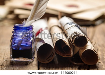 Closeup of old scrolls and blue ink in the inkwell