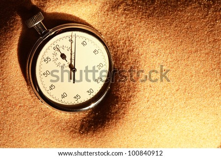Closeup of old stopwatch on sand surface with free space for text
