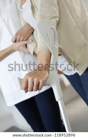 Closeup of old woman's hands leaning on crutches