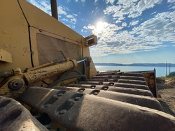 Closeup of old yellow bulldozer on dirt near lake with blue sky and lens flare