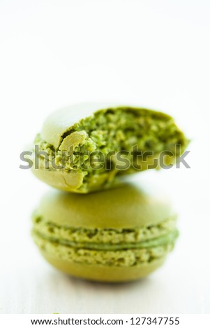Closeup of one full and one half eaten green pistachio macaroon