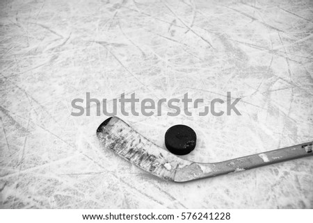 Closeup of one hockey stick and puck laying on textured ice in black and white