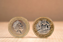 Closeup of  One Pound sterling coin standing on wooden table background.