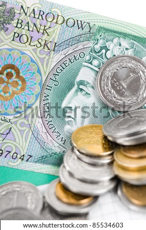 Closeup of one value polish zloty banknote and coins lying on green banknote, coins blurred, vertical orientation, nobody.