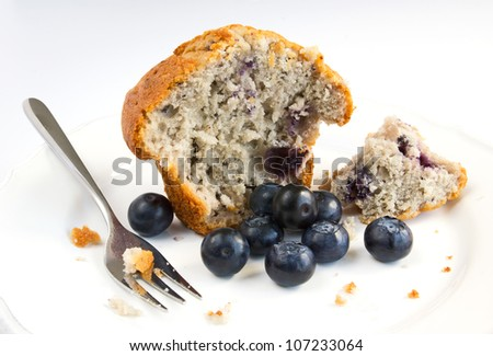 Closeup of open blueberry muffin with fresh blueberries and fork on a white plate