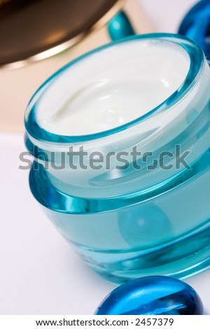 Closeup of open container of cosmetic face cream on white backround with small blue marbles around out of focus