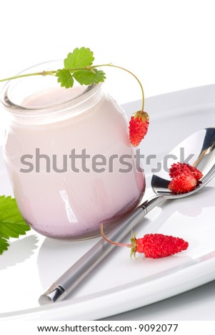 Closeup of open jar of organic yogurt and delicious wild strawberries