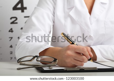 Closeup of ophthalmologist's hands writing a prescription