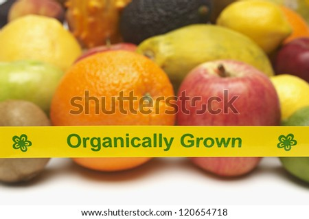 Closeup of organically grown fruits behind yellow tape over white background