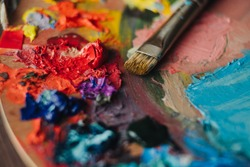 Closeup of paint mixing process in art workplace.