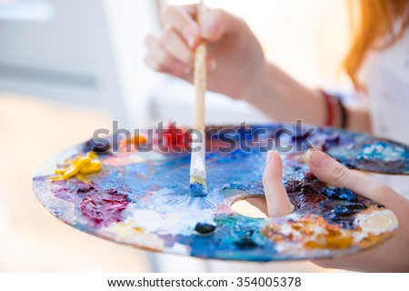 Closeup of paintbrush in woman hands mixing paints on palette #354005378