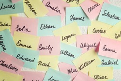 Closeup of paper stickers with different names on white wall. Concept of choosing baby name