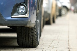 Closeup of parked car on a city street side with new winter rubber tires.