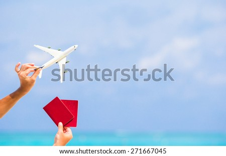 Closeup of passports and white airplane background the sea - Shutterstock ID 271667045