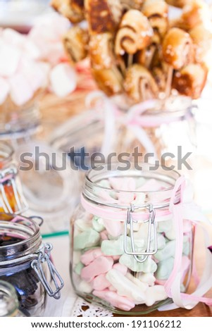 Closeup of pastel colored marshmallows in glass jar with decorative ribbon with small snack sized cinnamon buns on sticks in a glass jar in background