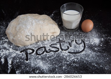 Closeup of pastry dough and egg with milk on black marble table with handwritten word on scattered flour