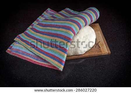 Closeup of pastry dough on baking board on black marble table covered by a dish-cloth view 1