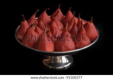 Closeup of pears poached in red wine and served in a silver colored bowl. A traditional Christmas dish in the Netherlands.