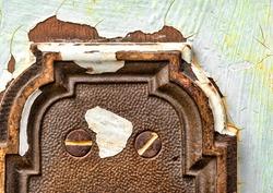 closeup of peeling paint and door plate