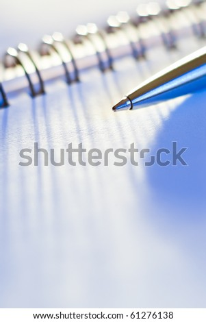 closeup of pen and business note-book in blue light