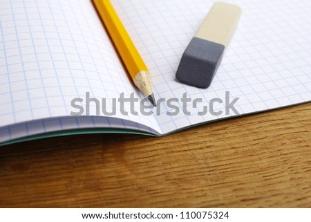 closeup of pencil notebook and eraser on wooden desk