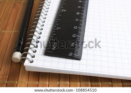 closeup of pencil, spiral notebook and ruler